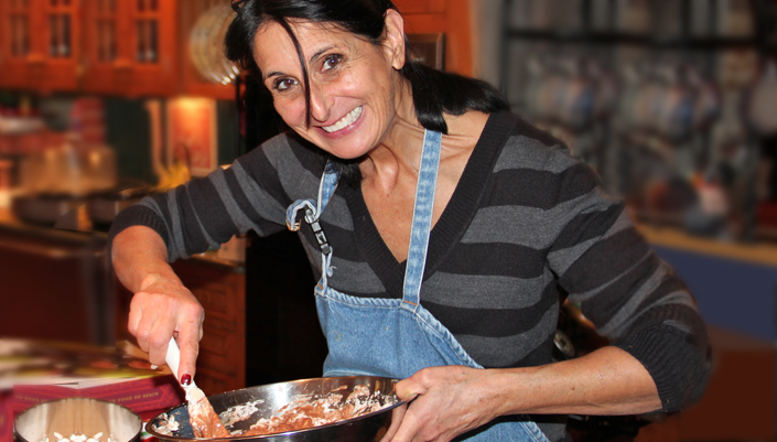 Dr David Katz Health Programs page: Catherine Katz stirring food as she cooks wearing a denim apron