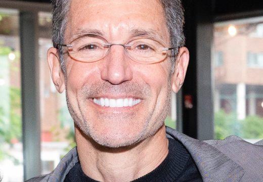 Dr. David Katz, smiling, in front of large windows, wearing black tee with gray blazer