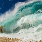 Huge wave of blue water and seafoam crashes on a brown sand and pepple-filled beach