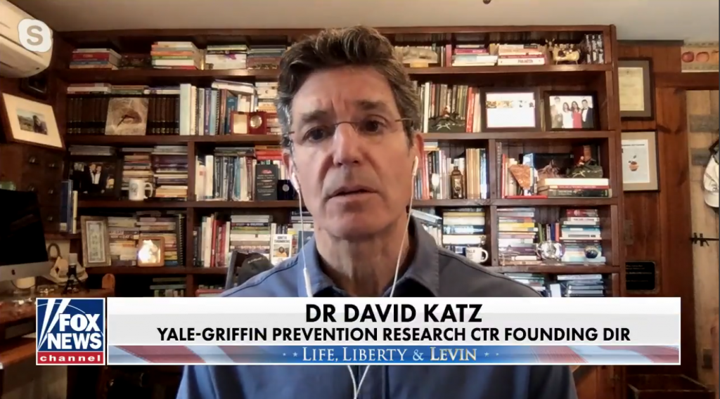 "Clip from the interview: Dr. Katz in his library, book shelf in background, ""Dr. David Katz, Yale-Griffin Prevention Research Center Founding Director"" caption at bottom."