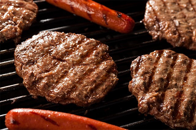 Close up of hot dogs and hamburgers on a grill