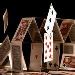 Image of a House of (Playing) Cards with the top ones falling over onto the table.