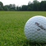 "Closeup of a golf ball on a fairway with ""Mulligan"" and the number 2 on it."