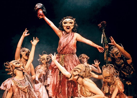 Opera scene. Main character sings above the others who are lauding the main character. All characters are dressed in brown/pink peasant garb and wear full-face theatrical masks.