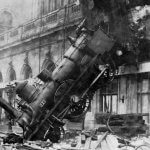 Black and white image of an early locomotive crashing into an old city building