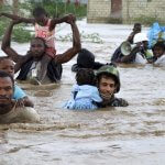 Black and brown military men saving young black children from flooding waters, carrying them through the water.